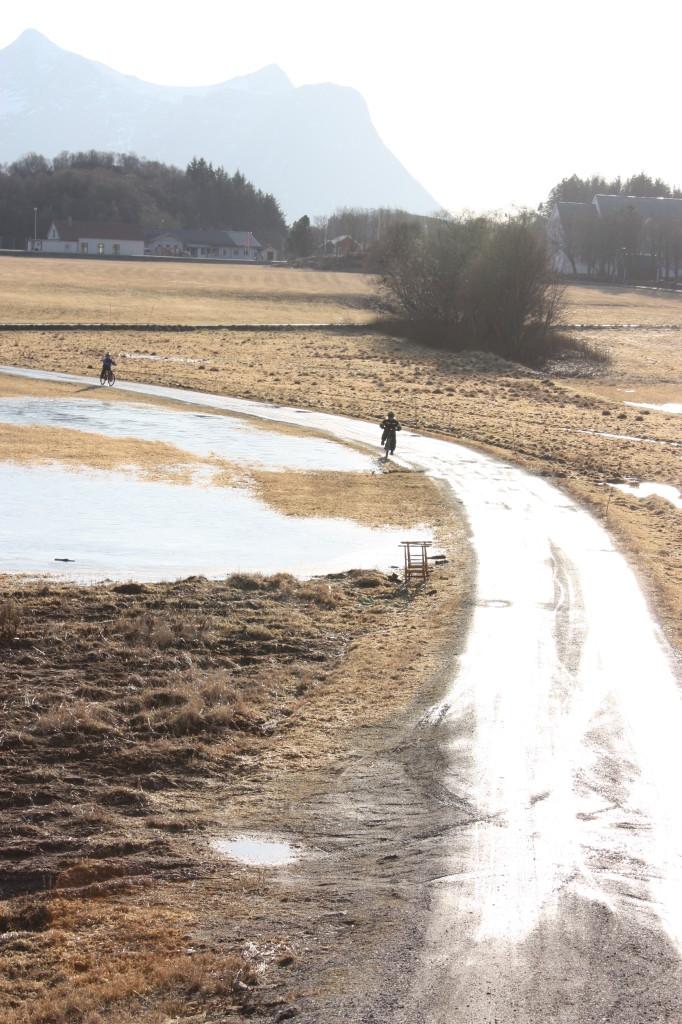 Veien er våt, og isen på marka er blitt en liten innsjø. Sparkene er byttet ut med sykler.